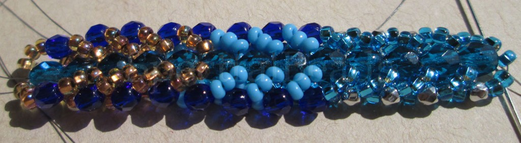 A sample of Flat Spiral stitch in blues, with some copper-lined beads introduced toward the end.