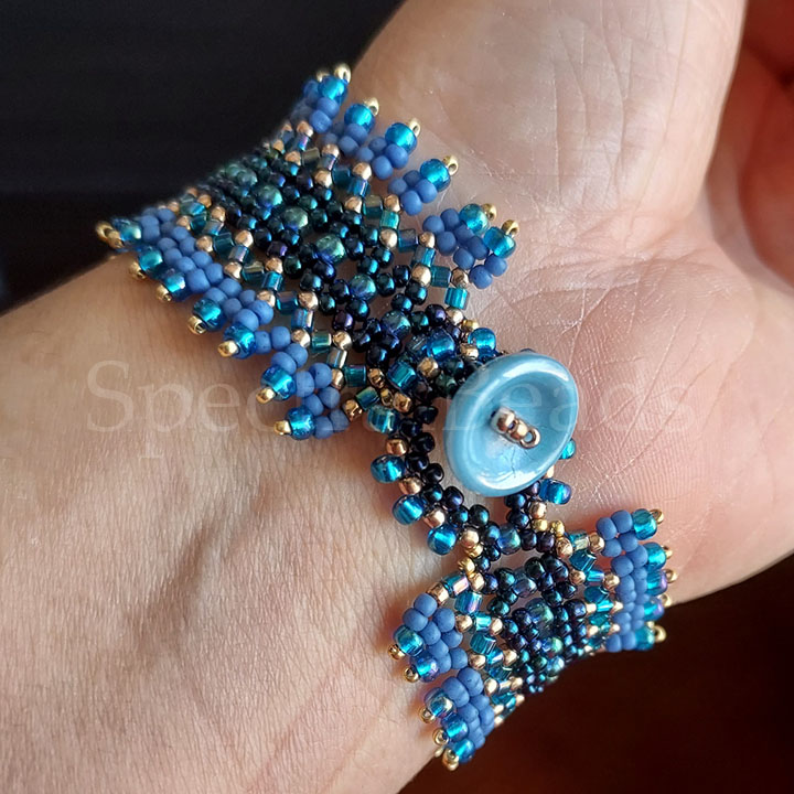 Close-up of a bracelet clasp on a wrist, showing a turquoise blue glass Potomac Cup Button.
