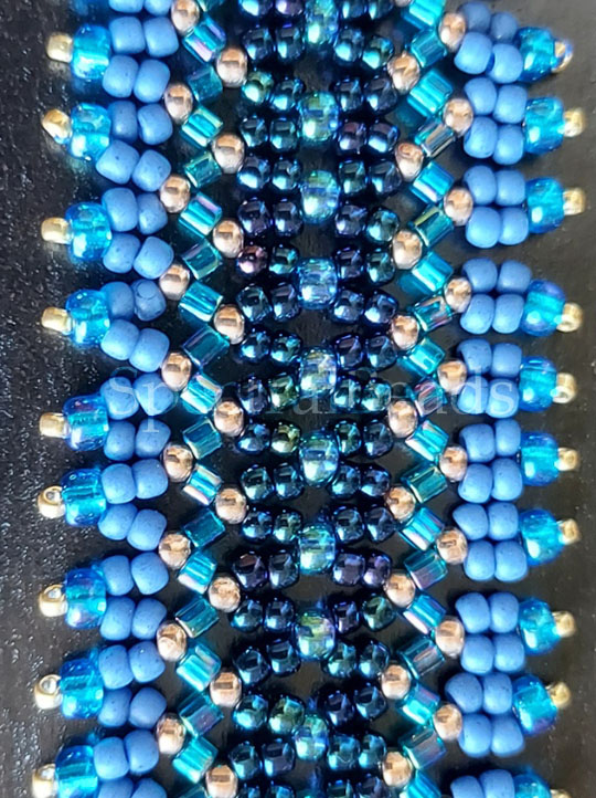 Detail of a bracelet band woven in Chevron Stitch out of beads in goldtone and multiple shades of blue.